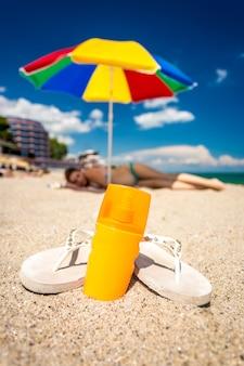 Primo piano di un paio di infradito e crema solare sdraiato sulla spiaggia sabbiosa