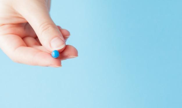 Colpo del primo piano della pillola nella mano degli infermieri isolata sopra l'azzurro