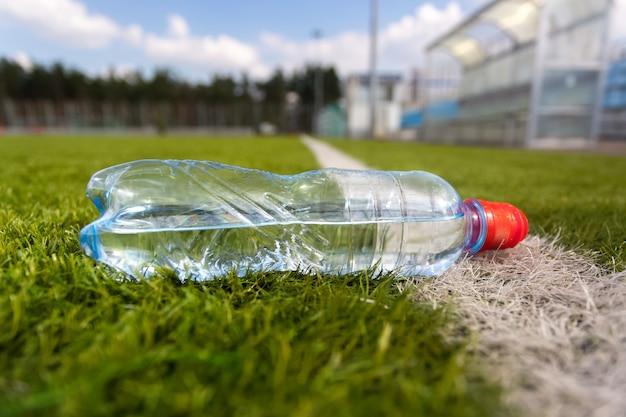 Colpo del primo piano della bottiglia di plastica di acqua che si trova sul campo di calcio dell'erba