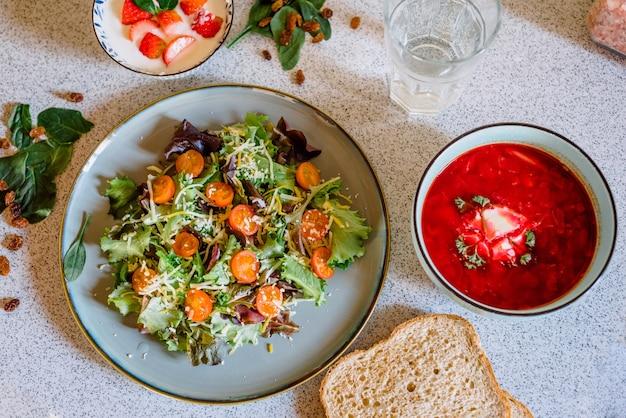 Colpo del primo piano di un piatto con un'insalata accanto a una ciotola di bor rosso