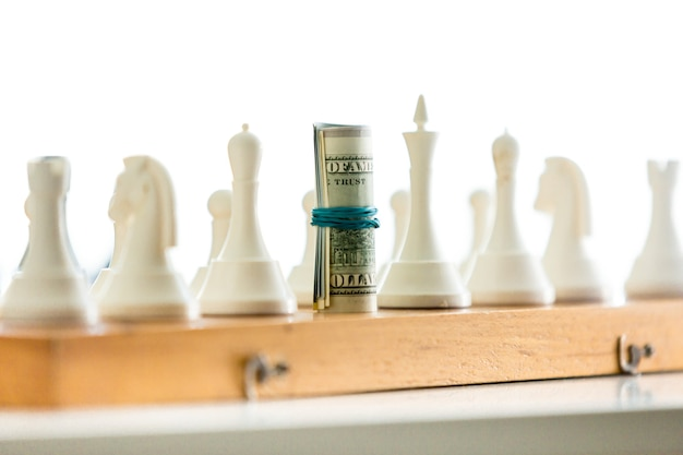 Colpo del primo piano di giocare a scacchi con banconote attorcigliate