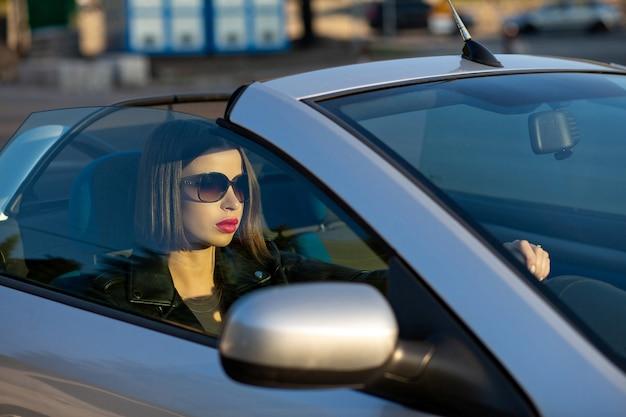 Colpo del primo piano di una bella donna bruna con le labbra rosse che indossano occhiali da sole alla guida di una cabriolet. spazio per il testo