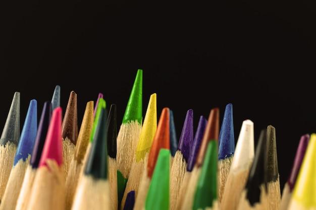 Primo piano delle punte affilate di matite scolastiche colorate su sfondo nero, copia spazio foto
