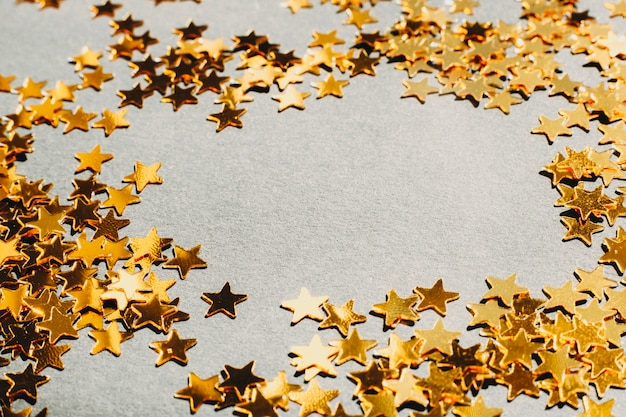 Colpo del primo piano di coriandoli a forma di stella lucidi che formano il confine sul piano del tavolo grigio chiaro