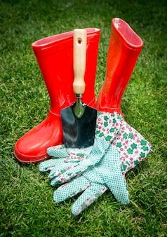 Colpo del primo piano di piccola vanga, guanti e stivali di gomma rossi che si trovano sull'erba verde