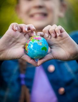 Primo piano di una ragazza sorridente che tiene il globo con le mani piegate a forma di cuore