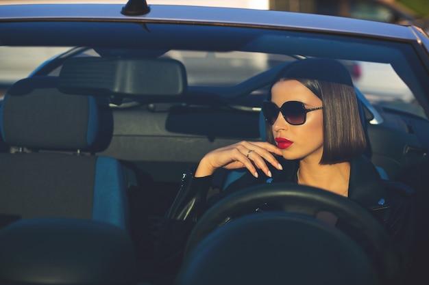 Colpo del primo piano della donna castana alla moda con le labbra rosse che indossano occhiali da sole che guidano un cabriolet. spazio per il testo
