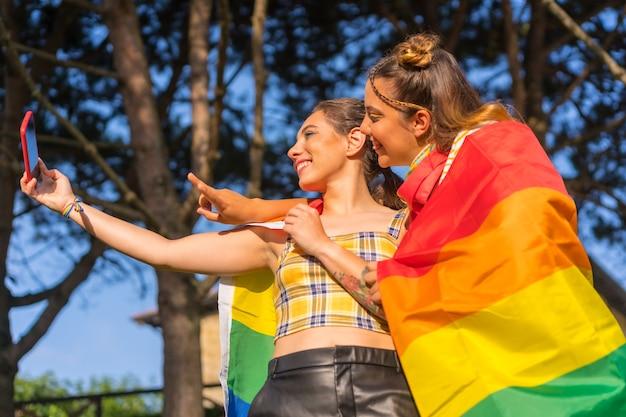Un primo piano di due giovani femmine caucasiche che si abbracciano con la bandiera dell'orgoglio lgbt che si fanno selfie all'aperto