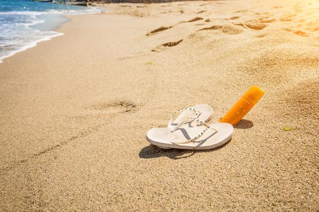 Colpo del primo piano delle pantofole bianche e della crema solare che si trovano sulla riva del mare