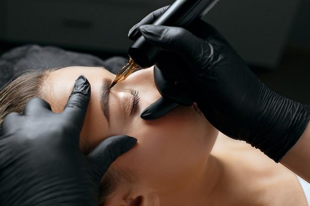 Colpo del primo piano di una donna in guanti neri che fa il trucco permanente della fronte a una giovane donna nel salone di bellezza