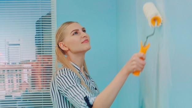 Colpo del primo piano del costruttore di donna al cantiere con rullo di vernice che lavora parete di pittura con bianco...