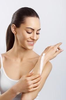 Colpo del primo piano delle mani della donna che applicano crema idratante per le mani