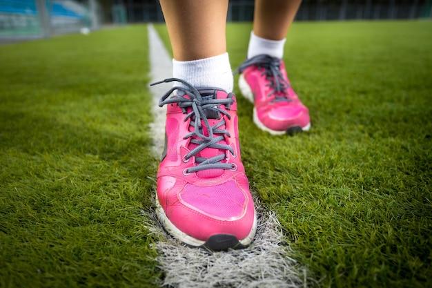 Colpo del primo piano della donna in scarpe da ginnastica rosa che corre sull'erba fresca fresh