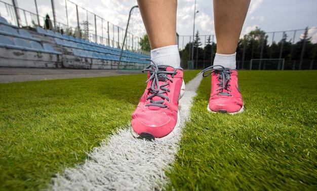 Colpo del primo piano della donna in scarpe da tennis rosa che corrono sul campo di erba