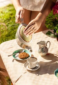 Colpo del primo piano della donna che versa il tè dalla pentola in tazza