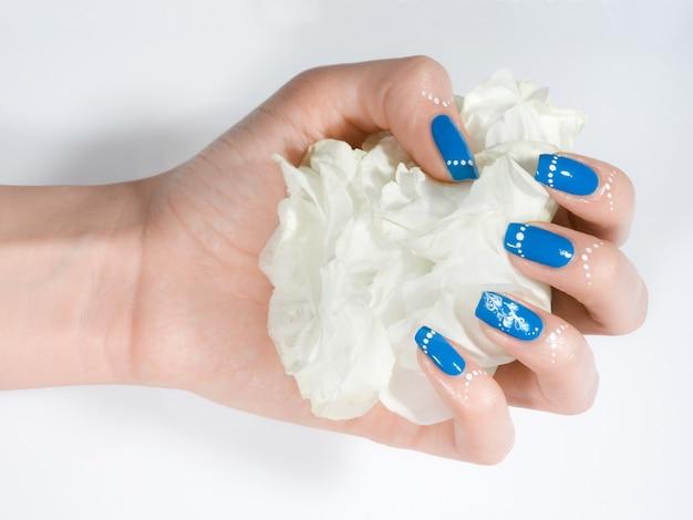 Colpo del primo piano della mano della donna con il manicure blu di inverno su priorità bassa bianca