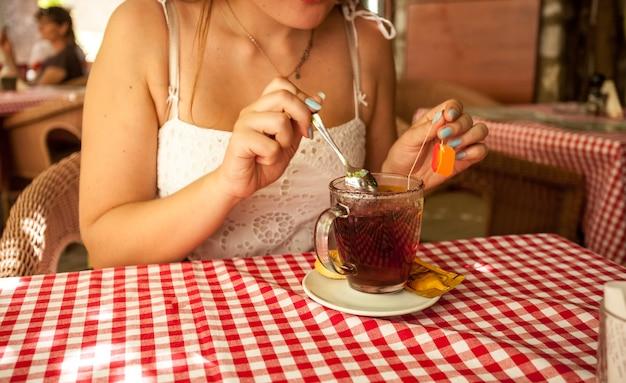 Colpo del primo piano della donna che mescola lo zucchero nel tè al caffè