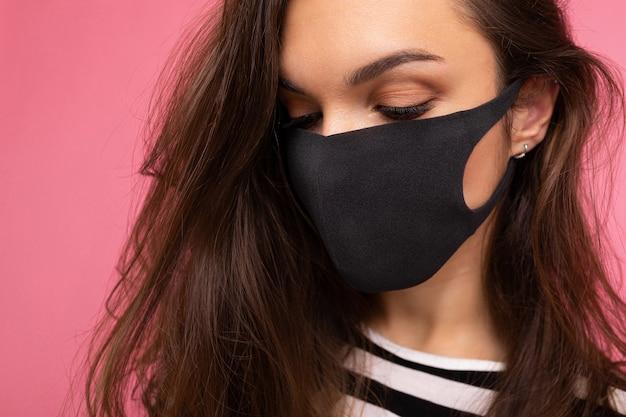 Colpo del primo piano di giovane bella donna in maschera protettiva riutilizzabile del virus sul viso contro il coronavirus isolato sul muro di sfondo rosa