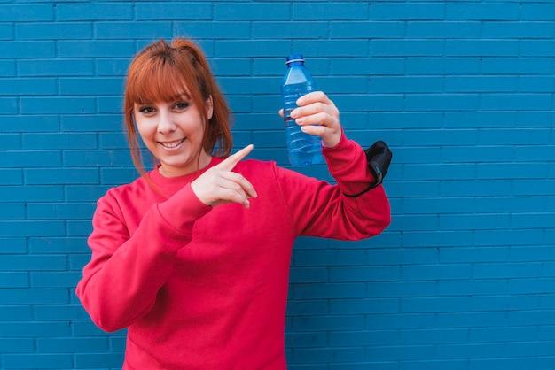 Colpo del primo piano di una giovane donna sportiva che tiene una bottiglia d'acqua