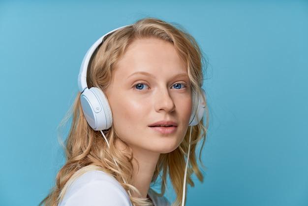 Ritratto di vista laterale del primo piano della giovane donna che ascolta la musica tramite le cuffie