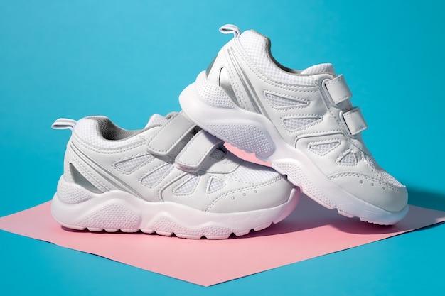 Vista laterale del primo piano di due sneakers bianche per adolescenti con chiusure in velcro su un quadrato geometrico di carta rosa ...