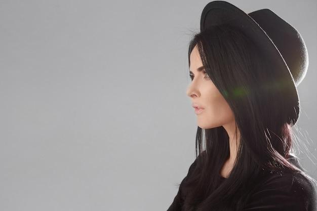Vista laterale del primo piano di una giovane donna modello con un cappello nero isolato sullo sfondo bianco