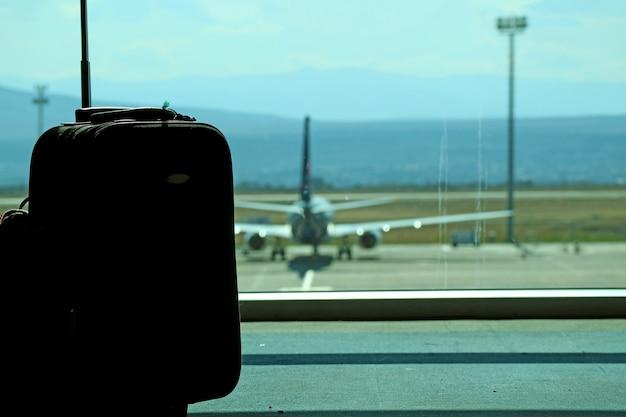 Primo piano silhouette di un bagaglio nella sala d'imbarco dell'aeroporto con aereo sfocato sullo sfondo