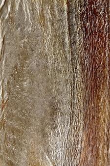 Primo piano della pelle argentea di pesce spada essiccato all'aria salato
