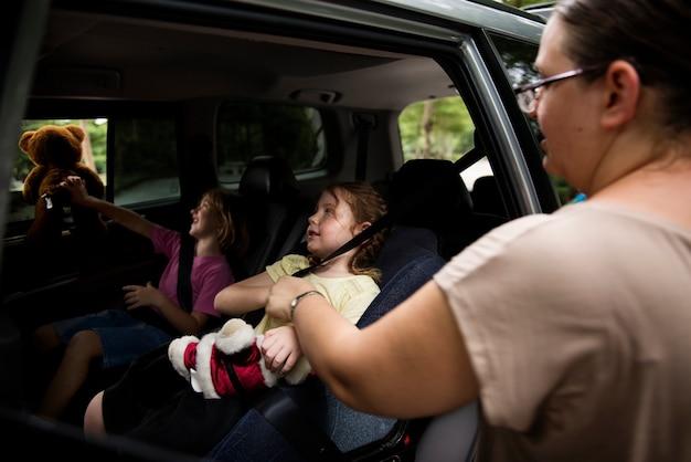 Primo piano delle sorelle che si siedono dentro l'automobile