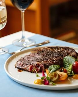 Primo piano sulla bistecca di manzo ribeye a fette con insalata di verdure fresche con vino rosso sul tavolo blu