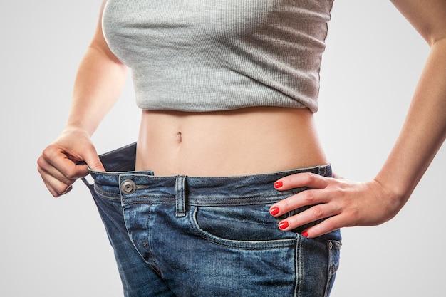 Primo piano della vita sottile della giovane donna in piedi in grandi jeans e top grigio che mostra perdita di peso di successo, colpo dello studio dell'interno, isolato su fondo grigio chiaro, concetto di dieta.