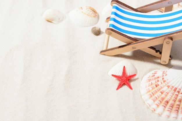 Primo piano del piccolo lettino prendisole e conchiglie di mare a disposizione sulla sabbia