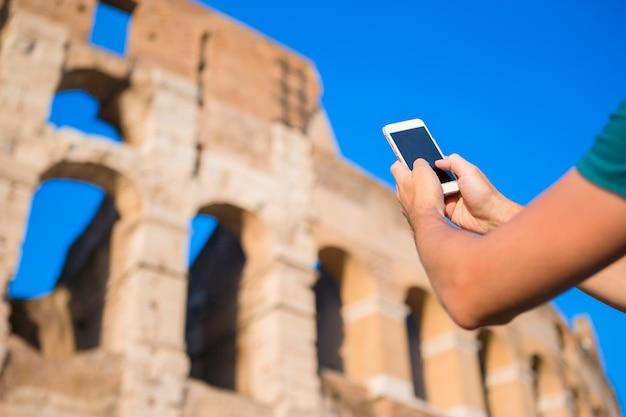 Smartphone del primo piano di grande colosseo, roma, italia