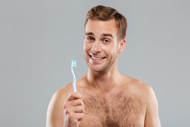 Giovane attraente sorridente del primo piano che tiene lo spazzolino da denti