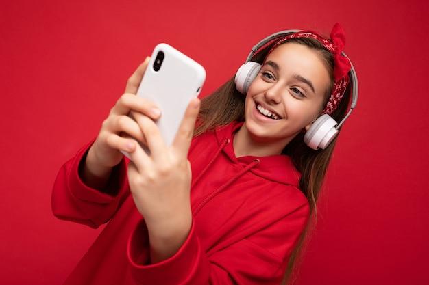 Ragazza castana attraente positiva sorridente del primo piano che porta la felpa con cappuccio rossa isolata sul rosso