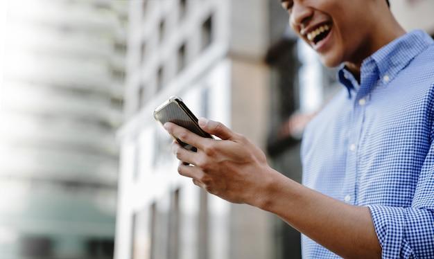 Primo piano di un giovane uomo d'affari asiatico sorridente utilizzando il telefono cellulare in città. immagine ritagliata e focus on hand