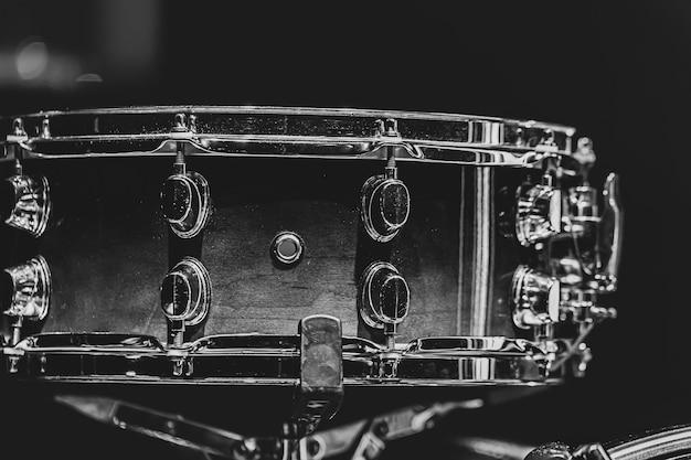 Primo piano di uno strumento a percussione del rullante su uno sfondo scuro