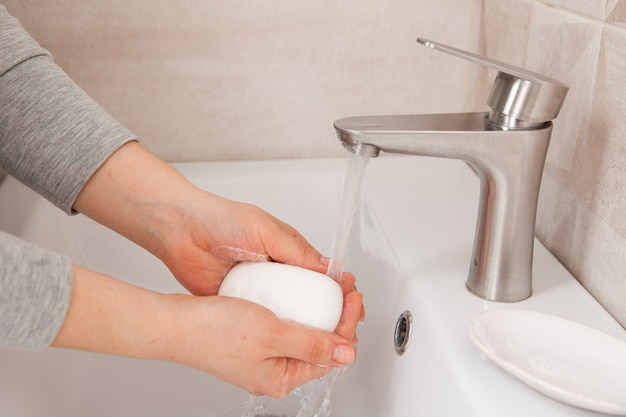 Mani femminili insaponate primo piano che tengono una barra di sapone. tenendo premuto per 20 secondi per distruggere completamente il virus sulle mani