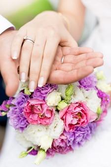 Primo piano foto soft focus dello sposo che tiene la mano della sposa sul bouquet da sposa