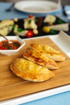 Primo piano sulle empanadas di torte spagnole con salsa sul tavolo del ristorante