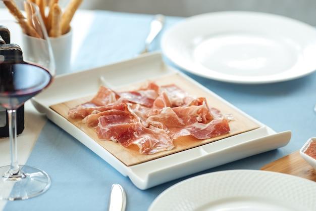 Primo piano sul jamon di maiale a fette spagnolo sul tavolo del ristorante