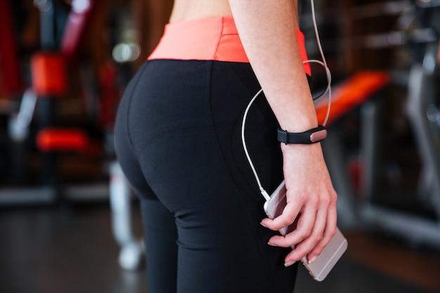 Primo piano di una sportiva con un fitness tracker sulla mano in piedi e che tiene il cellulare in palestra