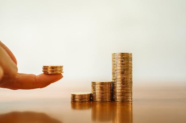 Primo piano della pila di monete d'oro con una pila di monete sul dito