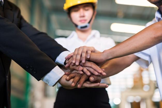 Mani della pila del primo piano per il concetto di lavoro di squadra in fabbrica. sinergia e lavoro di squadra per avere successo nell'industria pesante o negli affari.