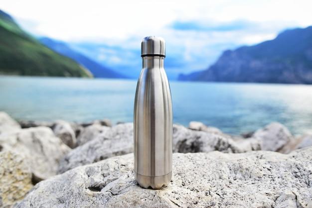 Primo piano della bottiglia d'acqua termica eco in acciaio sullo sfondo del lago in montagna