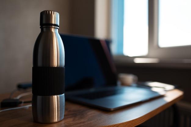 Primo piano della bottiglia di acqua termica riutilizzabile in acciaio su sfondo sfocato del computer portatile. concetto di spazio di lavoro. foto scura.