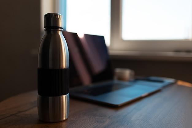 Primo piano della bottiglia di acqua termica riutilizzabile in acciaio su sfondo sfocato del computer portatile. concetto di spazio di lavoro.