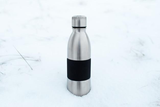 Primo piano della bottiglia d'acqua termo riutilizzabile in acciaio nella neve.