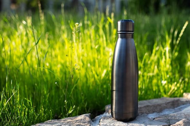 Primo piano della bottiglia d'acqua termica in acciaio di nero su sfondo di erba verde con spazio di copia. bottiglie riutilizzabili zero rifiuti eco concept plastic free.