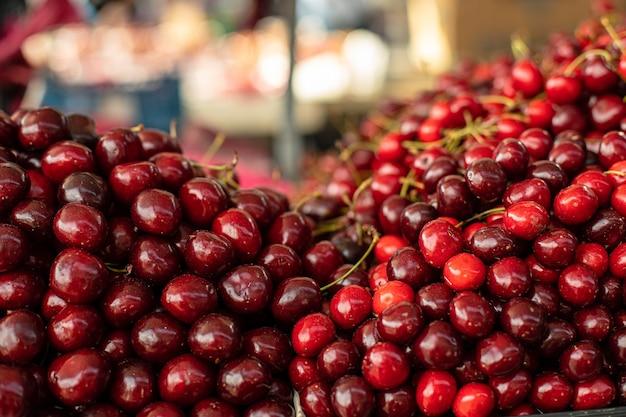 Primo piano stock foto di cumuli di ciliegie fresche mature in vendita presso il mercato locale all'ingrosso.